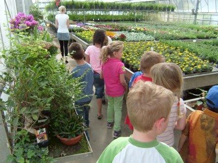 Kinder besichtigen ein Treibhaus mit Blumen