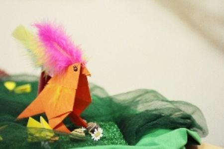 ein aus Papier und Federn gebastelter Vogel