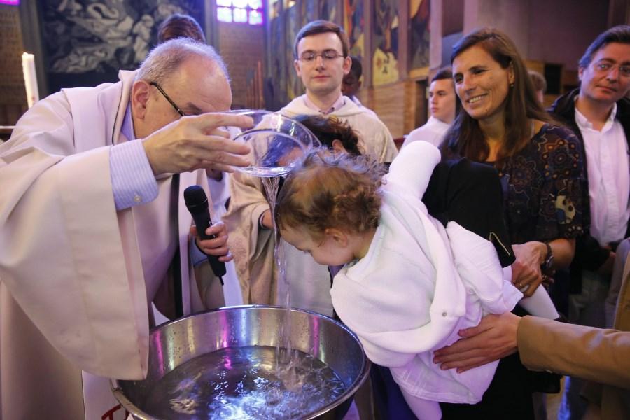 Priester tauft Kleinkind