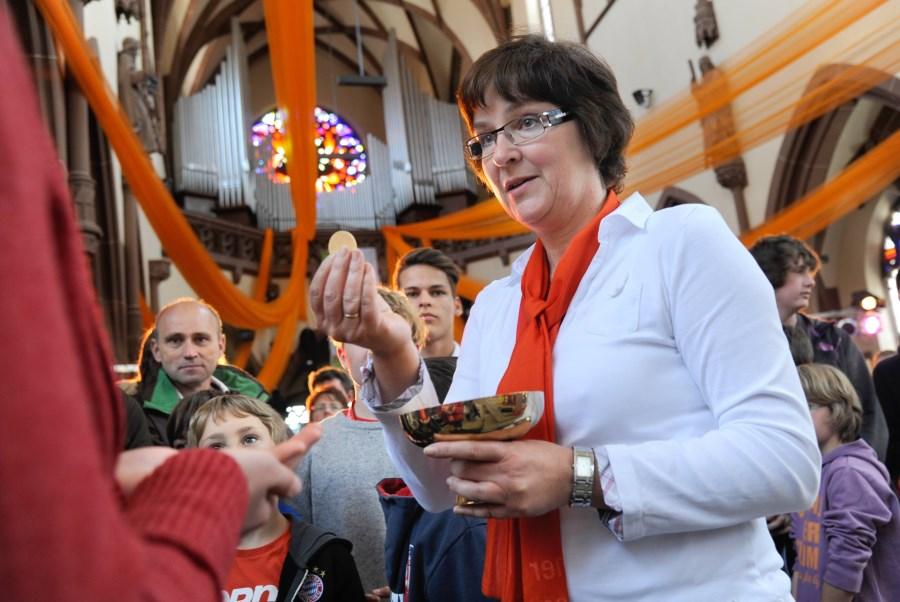 Ein Kommunionausteilerin bei der Messe