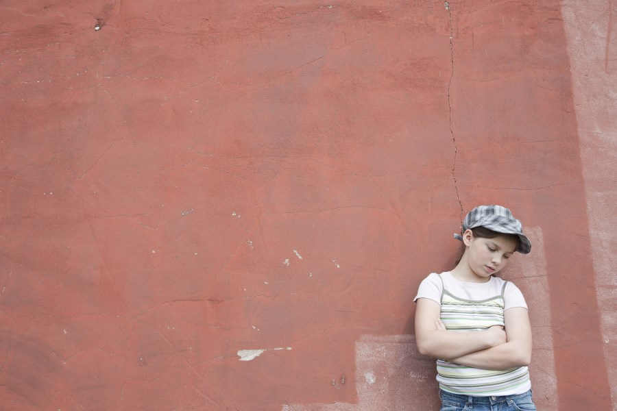 trauriges Mädchen an Wand