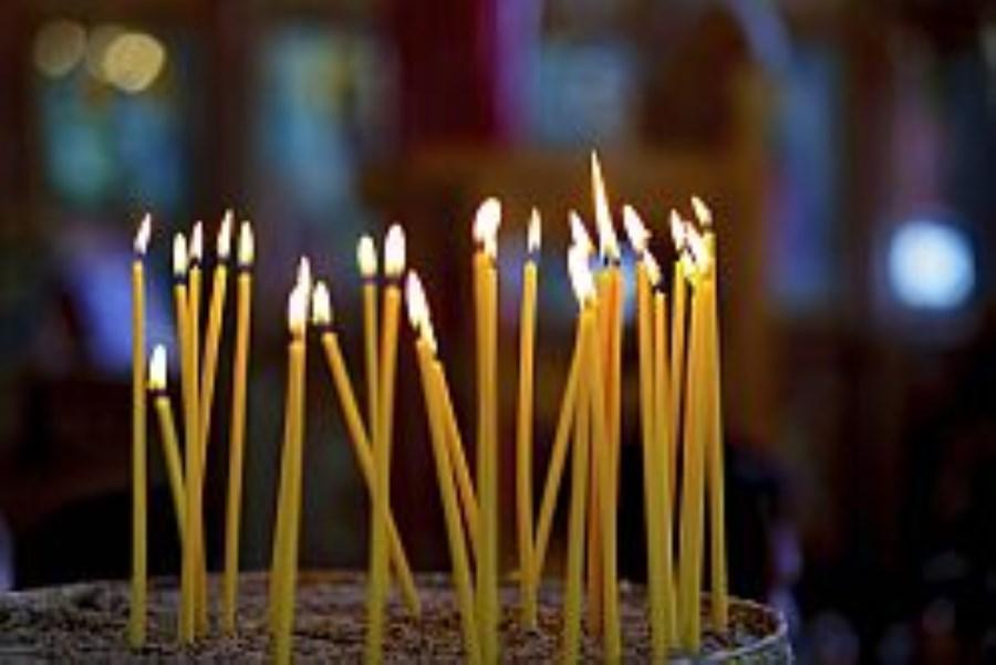 Viele lange Kerzen brennen in einer Schale mit Sand