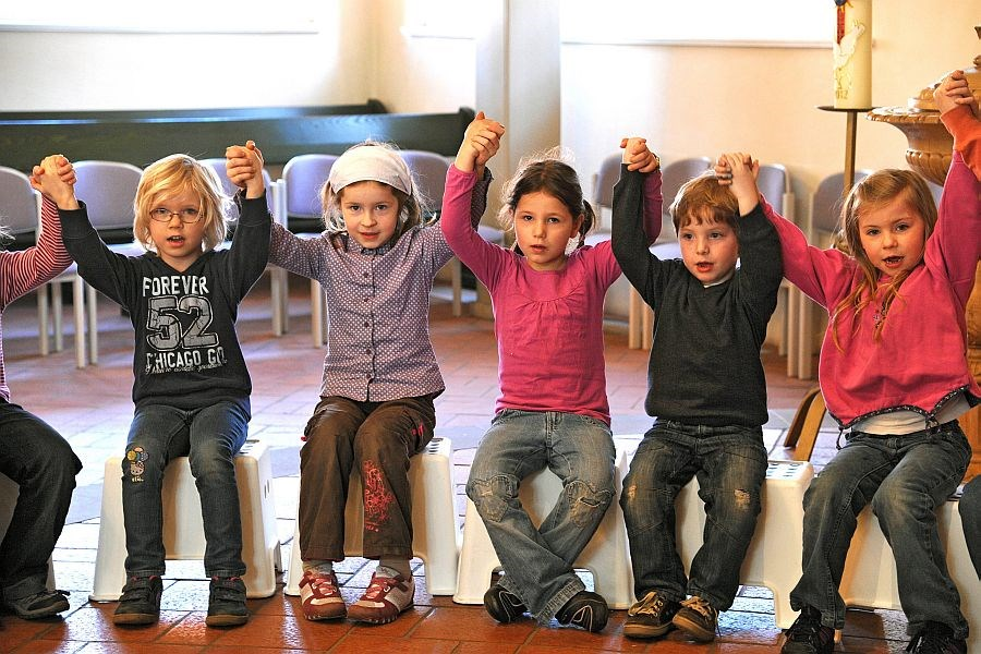 Kinder halten sich im Kindergottesdienst an den Händen