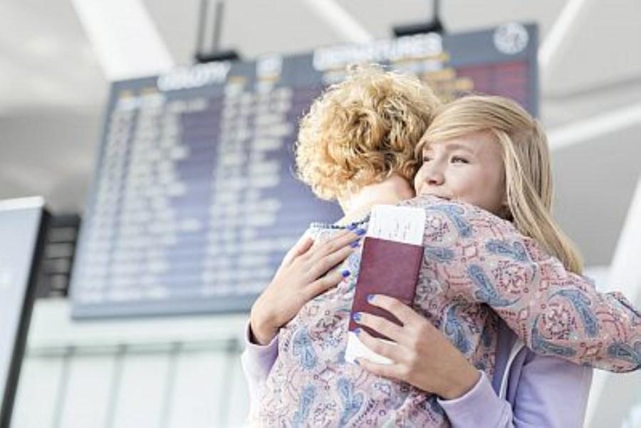 Mutter und Tochter umarmen sich am Flughafen