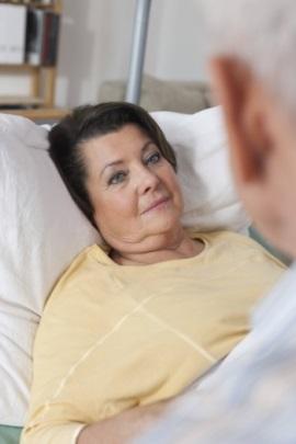 ältere Frau im Krankenhausbett im Gespräch mit Seelsorger
