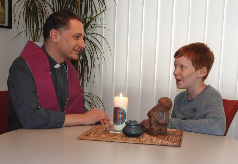Priester und Junge beim Beichtgespräch