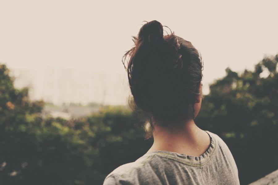 Mädchen im Teenageralter mit Dutt im T-Shirt sitz mit dem Rücken zur Kamera, entspannt. Blickt über eine entfernte unscharfe Stadtlandschaft mit Bäumen.