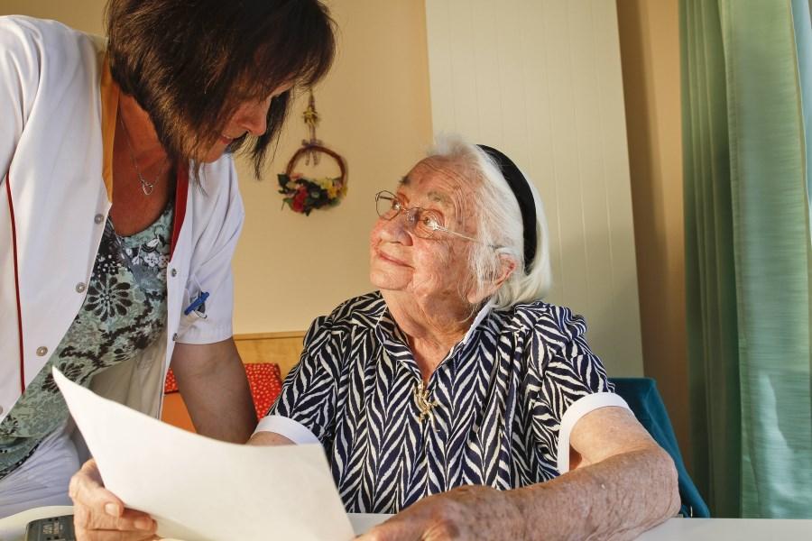 alte Frau mit Betreuerin im Pflegeheim am Tisch mit Papieren freundlich lächelnd