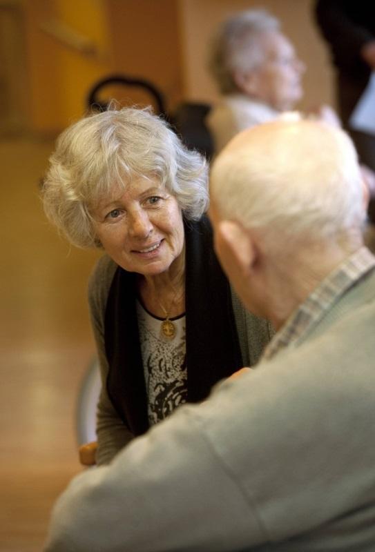 ältere Frau widmet sich freundlich altem Mann im Altenheim zu