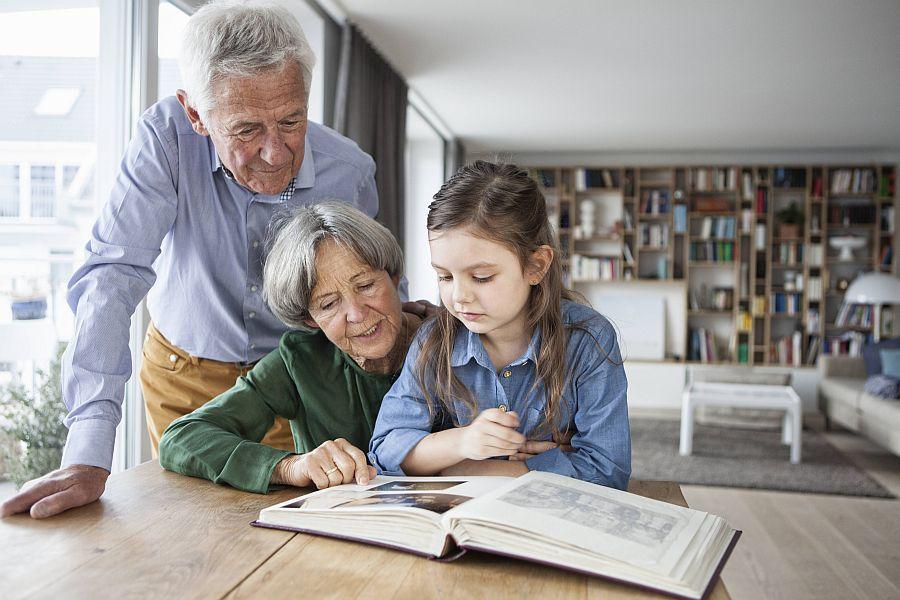 Großeltern schauen mit Enkelin ein Fotoalbum an