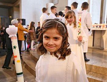 Erstkommunionkind mit Kerze