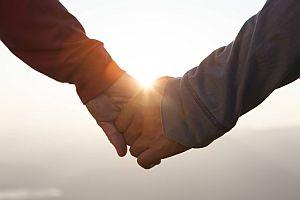 Zwei Hände halten sich im Gegenlicht