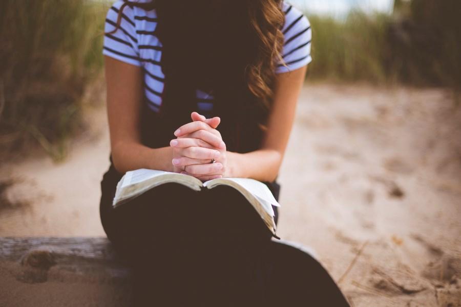 betende Haende junger Frau im Freien