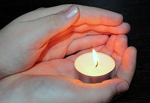 Zwei Hände umfassen schützend ein brennendes Teelicht