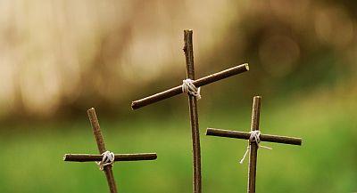 drei Kreuze aus Weidenstöcken, die mit Bindfaden zusammengebunden sind