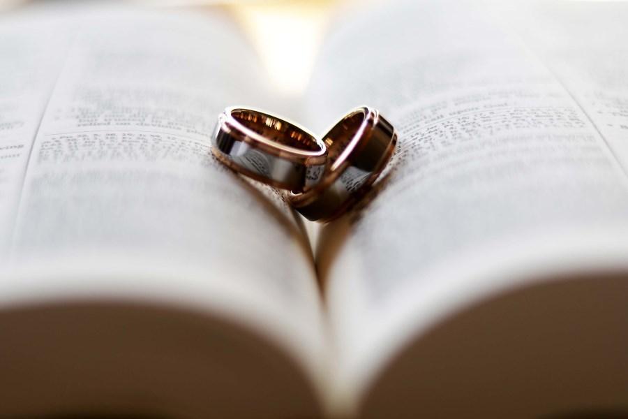 Eheringe auf aufgeschlagener Bibel bilden mit Schatten ein Herz
