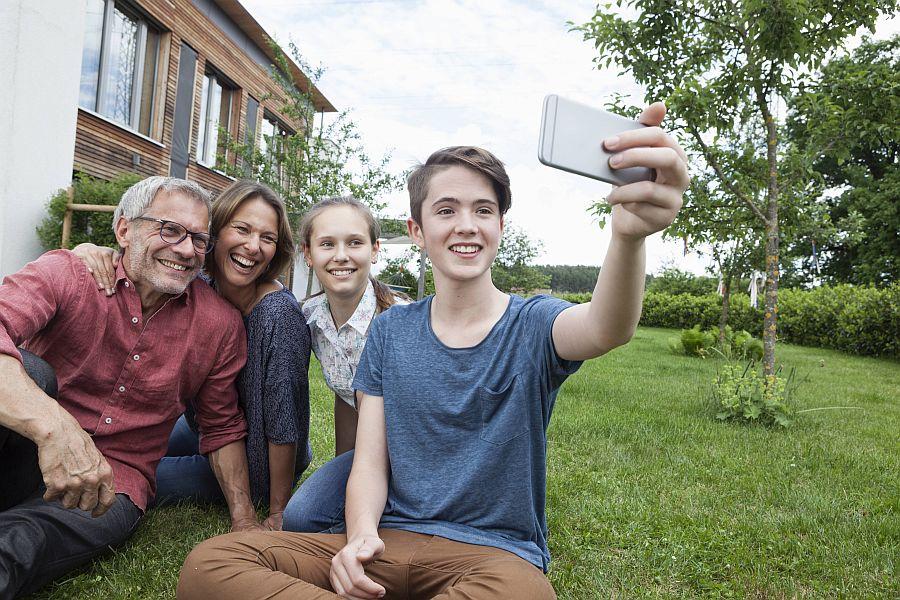 Familie mit Teenagern macht Selfie im Garten.