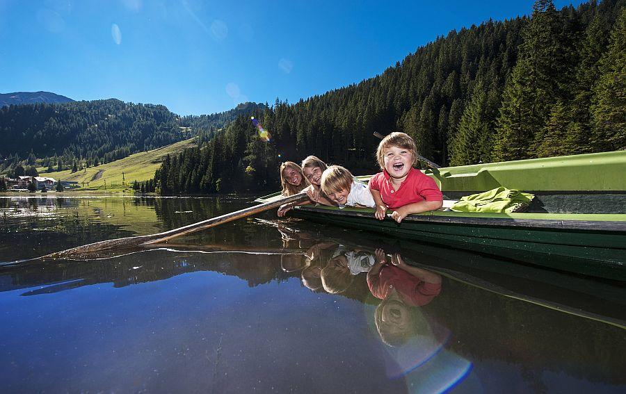 Kinder liegen entspannt in einem Ruderboot, das auf einem Bergsee treibt.