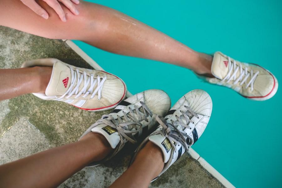 Beine Jugendlicher am Poolrand mit Sneaker