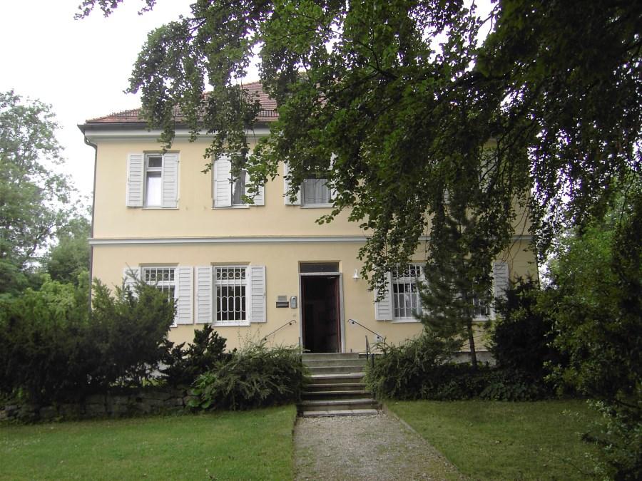 Das Pfarrhaus von außen, Weg und geöffnete Tür