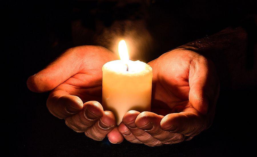 Zwei Hände umschließen eine brennende Kerze wie eine Schale.