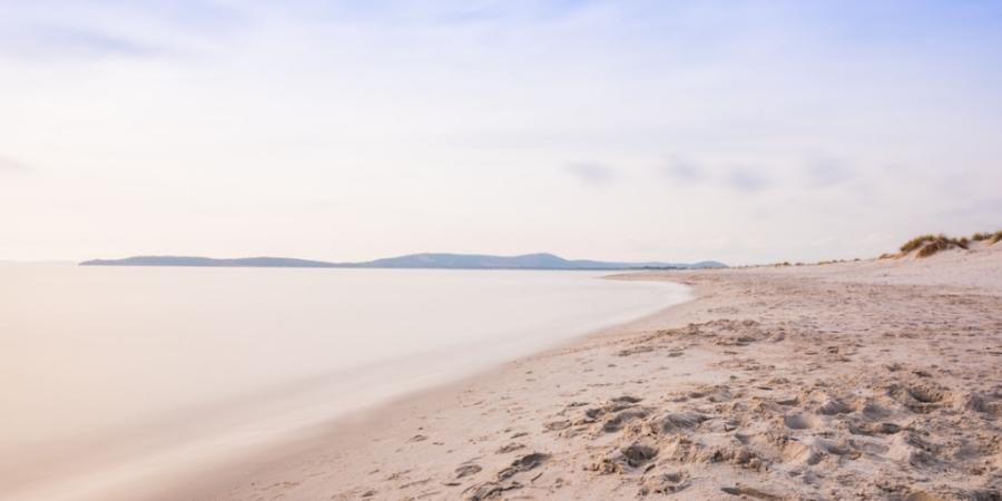 Fußspuren im Sand am Meer in leichten Pastelllicht