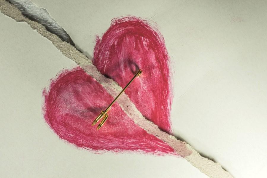 gemaltes rotes Herz mit Trennungsstrich verbunden mit Sicherheitsnadel