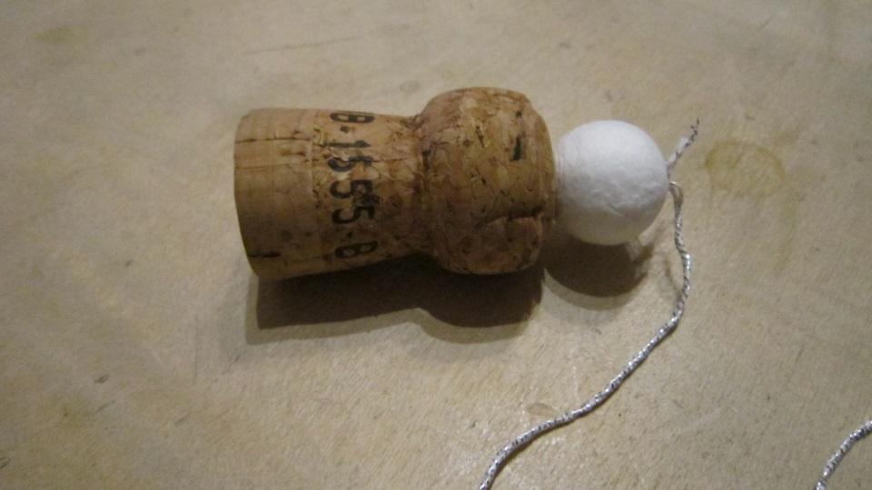 Nadel mit Glitzerfaden durch Baumwollkugel und Korken gestochen