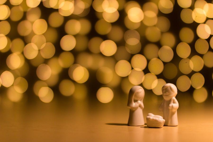 Figuren Heilige Familie vor diffusem Lichtermeer