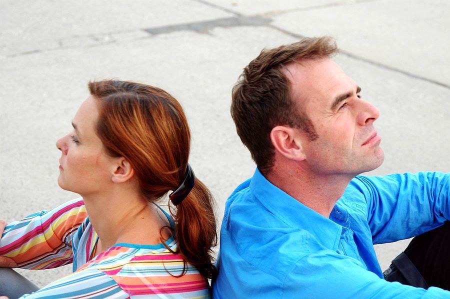 Mann und Frau sitzen Rücken an Rücken und schweigen sich an