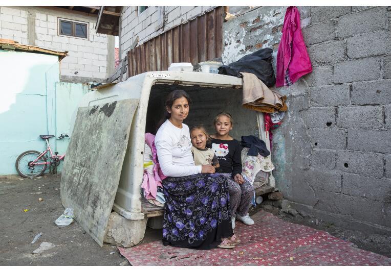 Roma-Mutter mit zwei Kinder vor rostigem Wagen, der ihr Zuhause ist