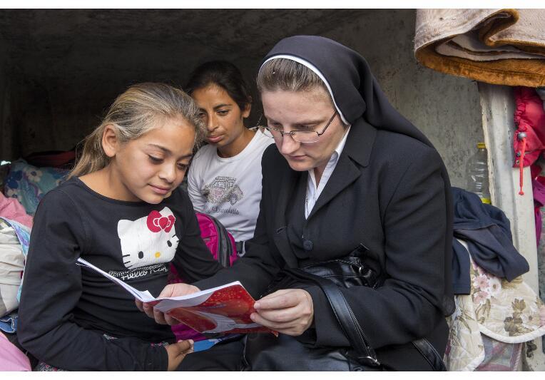 Schwester Adina freut sich, als die Kinder ihr im Schutzhaus ihre Schulhefte zeigen.