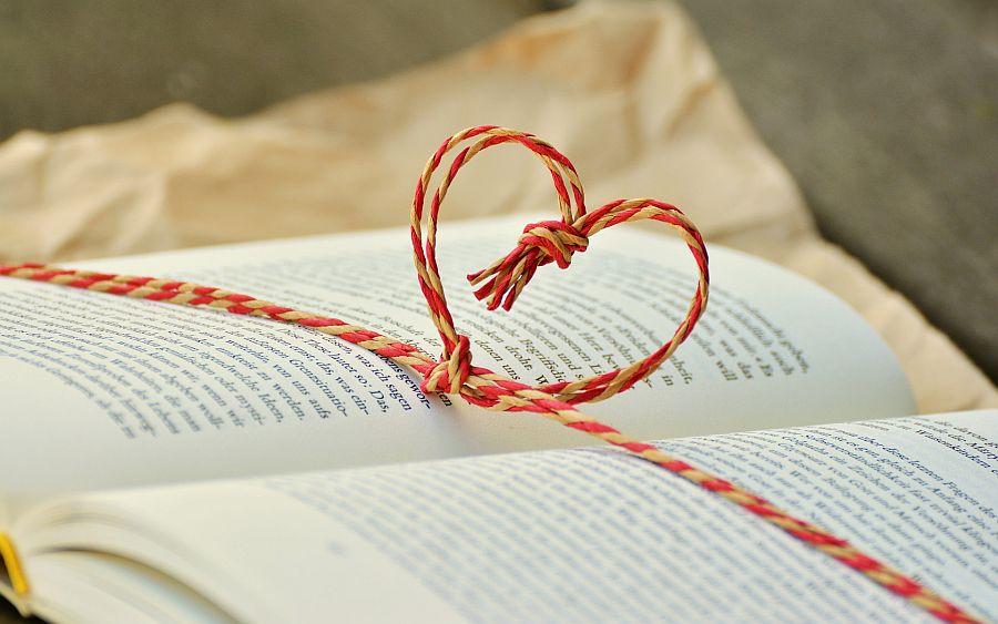 Auf einem Buch liegt eine zu einem Herz gebundene Kordel
