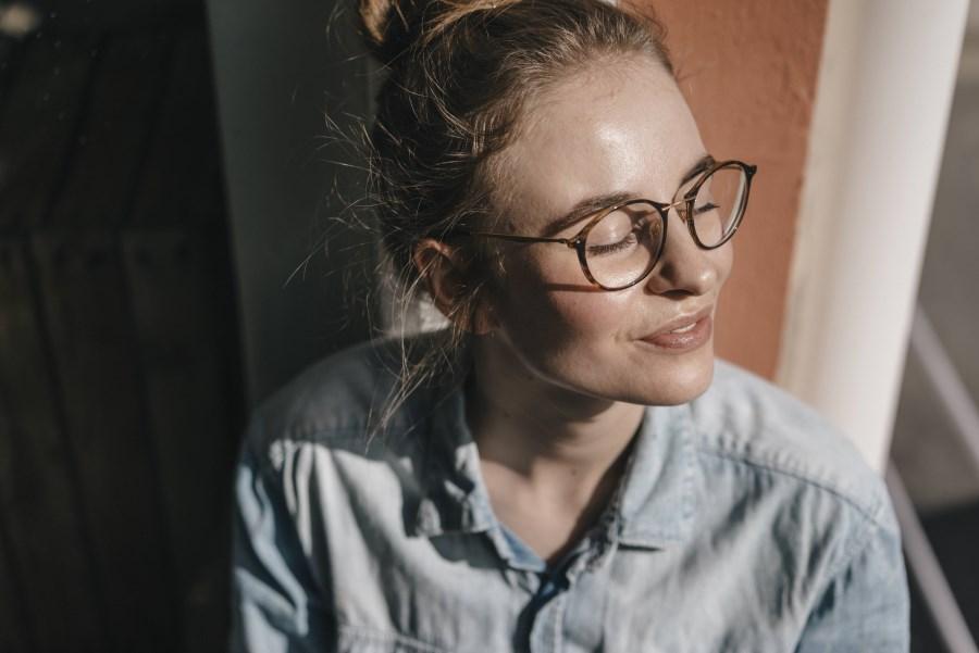 junge Frau mit Brille genießt Sonnenschein durchs Fenster