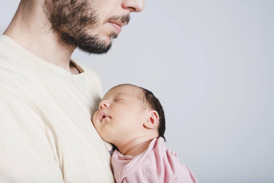junger Vater hält schlafendes Baby an der Brust