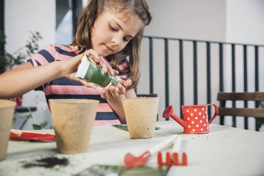 Mädchen sät Samen in kleinen Blumentopf