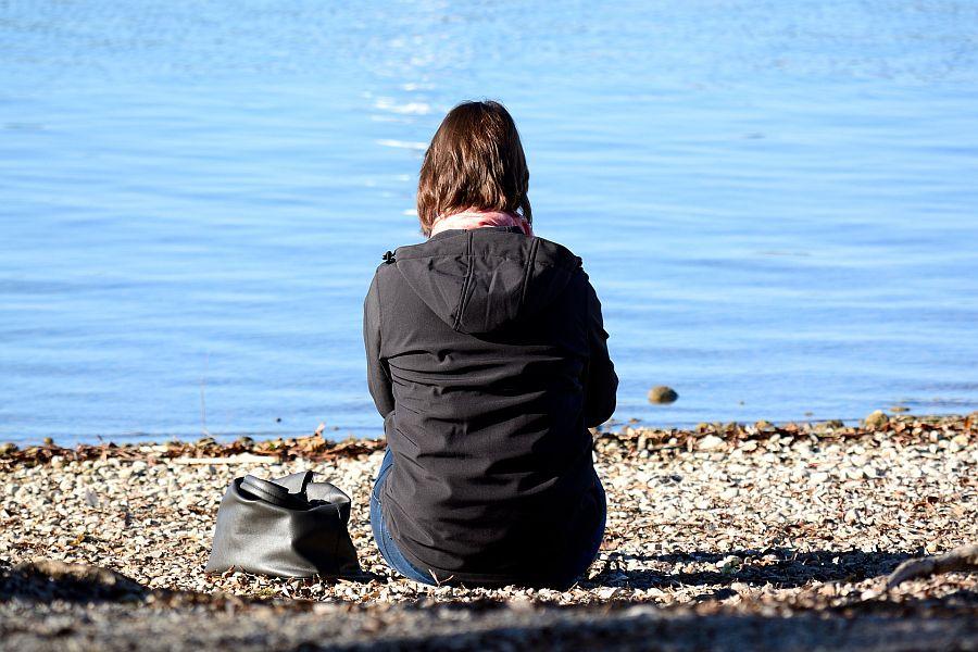 Frau in Jacke und Mütze sind mit dem Rücken zum Betrachter am See