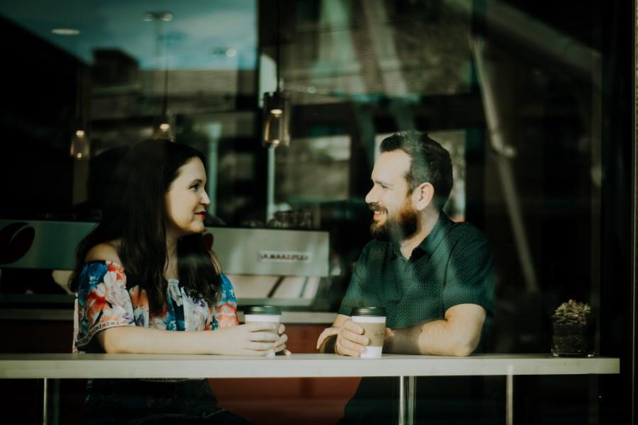 Mann und Frau im Gespräch im Lokal durch Scheibe fotografiert