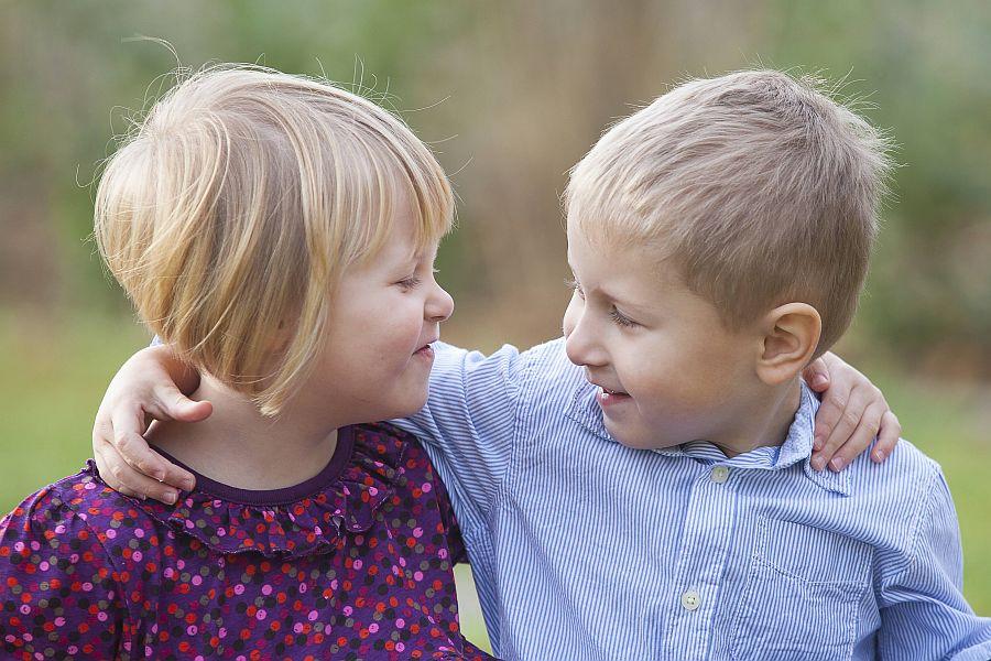 zwei kleine Kinder haben sich die Arme um die Schultern gelegt und lachen sich an