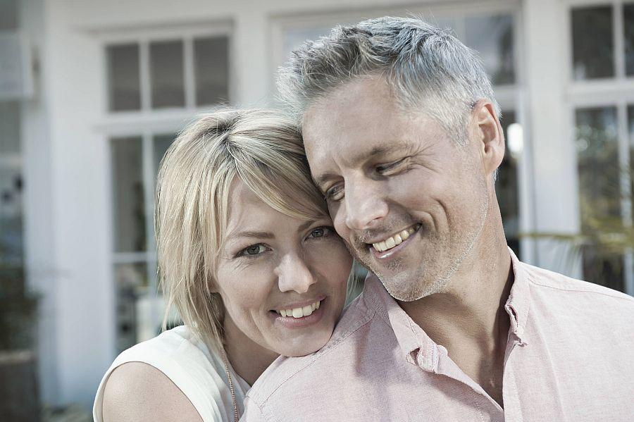 Frau legt ihren Kopf auf die Schulter ihres Mannes, der sie liebevoll ansieht