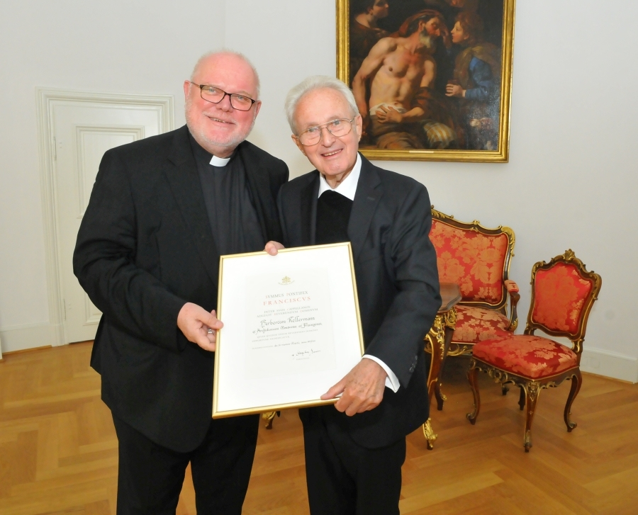 Kardinal Marx überreicht Pfarrer Herbert Kellermann die Ernennungsurkunde zum Monsignore