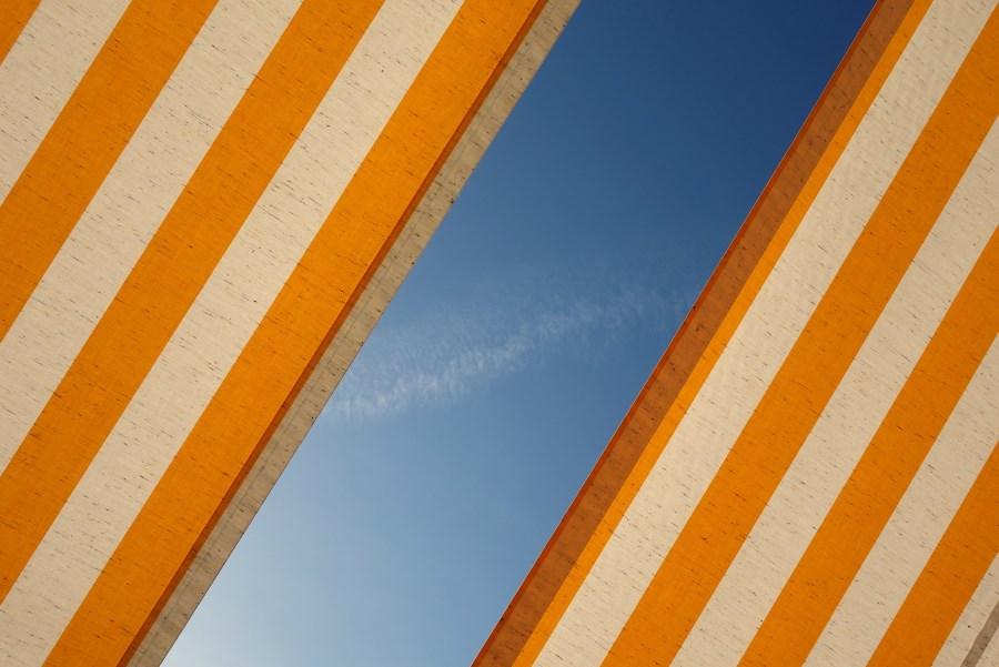 orange-weiß-gestreifte wände diagonal durch blauen himmel getrennt