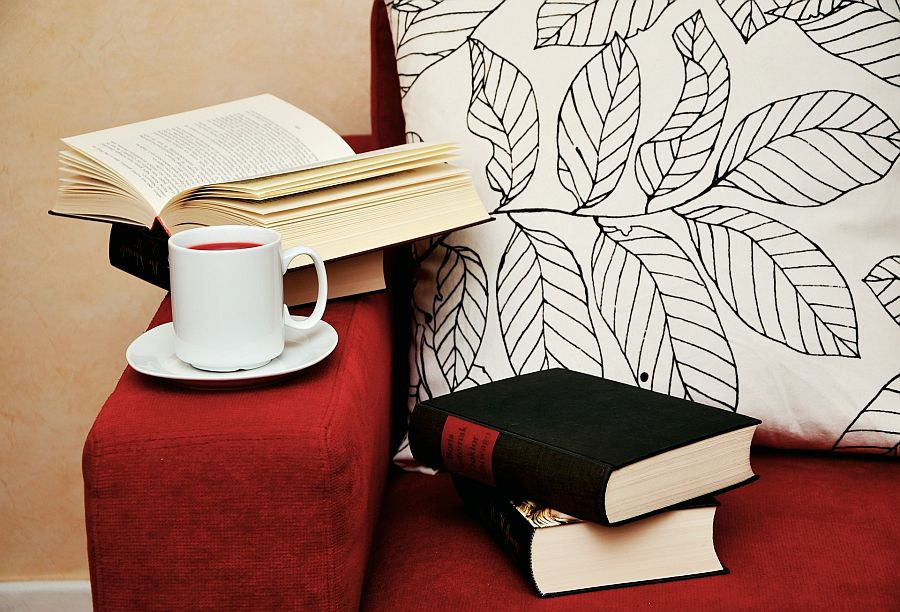 Bücher und eine Tasse Tee auf rotem Sofa