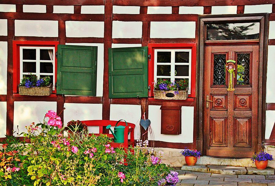 Eingangsbereich eines Fachwerkhauses mit verzierter Holztür, roten Fensterrahmen, einer Bank und Blumen