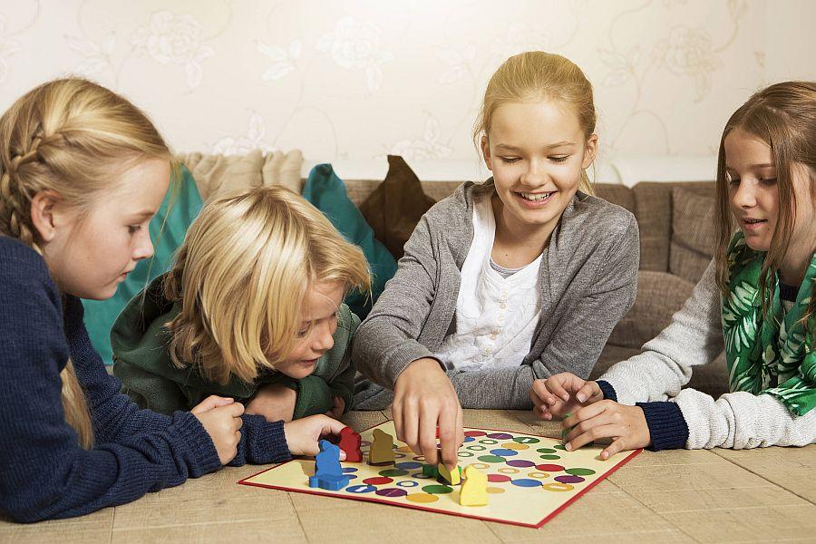 Vier Kinder spielen zusammen ein Brettspiel