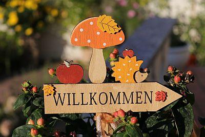 Herbstlich verziertes Holzschild im Garten mit der Aufschrift Willkommen