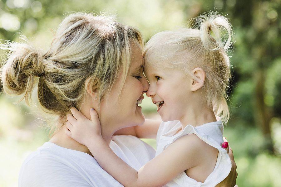 Mutter und kleines Mädchen umarmen sich liebevoll und stupsen ihre Nasen aneinander