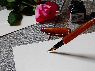 Briefpapier, Füller, Tintenfass und Rose auf Schreibtisch