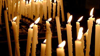 Brennende, schmale, gelbe Kerzen in einem Sandbehälter in einer Kirche