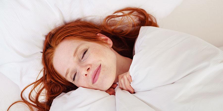 Frau mit roten Haaren kuschelt im Bett
